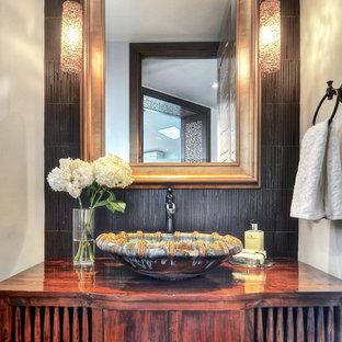 Ejemplo de aseo exótico, pequeño, con lavabo sobreencimera, armarios tipo mueble, puertas de armario de madera en tonos medios, encimera de madera, baldosas y/o azulejos marrones, paredes negras y encimeras marrones