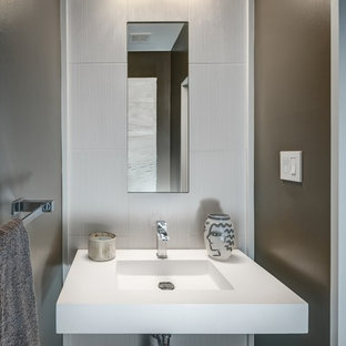 Example of a trendy gray tile and porcelain tile dark wood floor powder room design in DC Metro with brown walls, an integrated sink and solid surface countertops