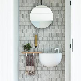 Неиссякаемый источник вдохновения для домашнего уюта: туалет в современном стиле с серой плиткой, плиткой мозаикой, белыми стенами, паркетным полом среднего тона, подвесной раковиной и коричневым полом