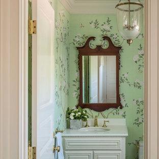 На фото: маленький туалет в классическом стиле с фасадами с выступающей филенкой, белыми фасадами, унитазом-моноблоком, зелеными стенами, паркетным полом среднего тона, врезной раковиной, мраморной столешницей, коричневым полом и белой столешницей с