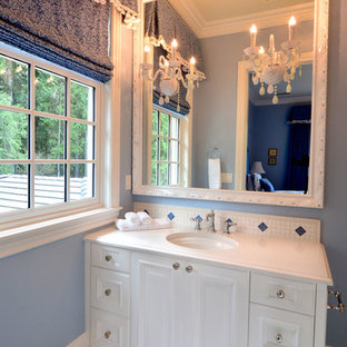 This is an example of a medium sized contemporary cloakroom in Seattle with flat-panel cabinets, white cabinets, multi-coloured tiles, marble tiles, blue walls, marble flooring, a submerged sink, limestone worktops and white floors.