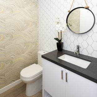Réalisation d'un WC et toilettes marin avec un placard à porte plane, des portes de placard blanches, un mur multicolore, un sol en bois clair, un lavabo encastré et un plan de toilette noir.