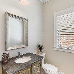 Esempio di un piccolo bagno di servizio minimal con ante a persiana, ante con finitura invecchiata, WC a due pezzi, pareti beige, parquet chiaro, lavabo sottopiano, top in cemento e pavimento beige