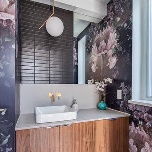Idées déco pour un WC et toilettes contemporain avec un placard à porte plane, des portes de placard en bois brun, un carrelage gris, un carrelage métro, un mur violet, une vasque, un sol violet et un plan de toilette beige.