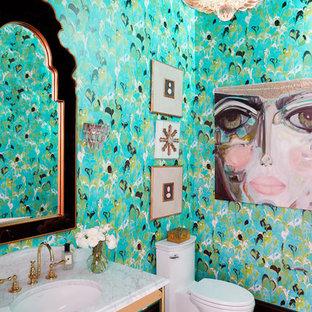 Diseño de aseo ecléctico con sanitario de una pieza, paredes azules, suelo de madera en tonos medios, lavabo bajoencimera, suelo marrón y encimeras blancas