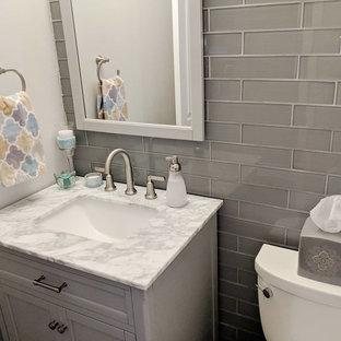 Неиссякаемый источник вдохновения для домашнего уюта: маленький туалет в современном стиле с плоскими фасадами, серыми фасадами, раздельным унитазом, синей плиткой, стеклянной плиткой, серыми стенами, полом из ламината, врезной раковиной, мраморной столешницей, серым полом и белой столешницей