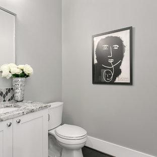 Aménagement d'un petit WC et toilettes craftsman avec un placard à porte shaker, un WC séparé, un carrelage gris, des carreaux de porcelaine, un sol en carrelage de porcelaine, un lavabo encastré, des portes de placard blanches, un mur gris et un plan de toilette en granite.
