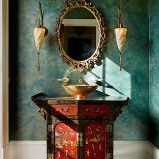 Cette image montre un WC et toilettes asiatique avec un placard en trompe-l'oeil, des portes de placard rouges, un mur vert, un sol en bois brun et une vasque.