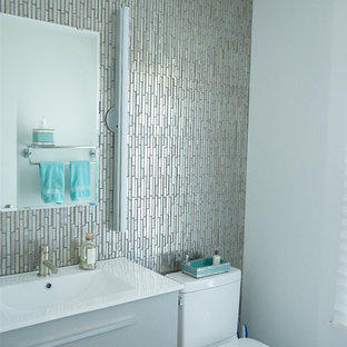 Small contemporary cloakroom in Minneapolis with freestanding cabinets, grey cabinets, a two-piece toilet, multi-coloured tiles, glass tiles, white walls, glass worktops and an integrated sink.