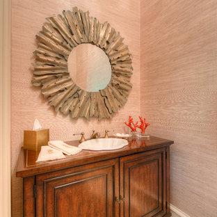 Aménagement d'un WC et toilettes classique avec un lavabo posé, un placard avec porte à panneau encastré, des portes de placard en bois brun, un plan de toilette en bois et un plan de toilette marron.