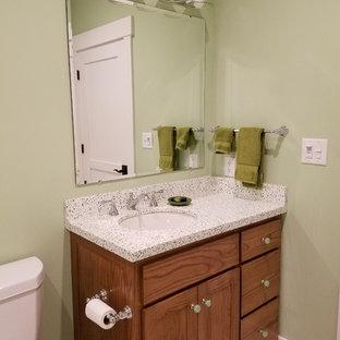 Idées déco pour un WC et toilettes classique de taille moyenne avec un placard en trompe-l'oeil, des portes de placard en bois brun, un WC séparé, un carrelage blanc, des carreaux de céramique, un mur vert, un sol en carrelage de terre cuite, un lavabo encastré, un plan de toilette en terrazzo et un sol beige.