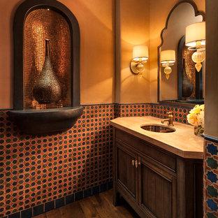 Réalisation d'un WC et toilettes méditerranéen avec un lavabo encastré, un placard en trompe-l'oeil, des portes de placard en bois sombre, un carrelage multicolore, un mur orange, un sol en bois foncé et un plan de toilette beige.