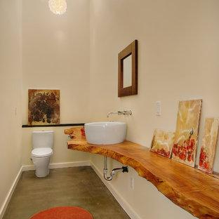 Идея дизайна: туалет в современном стиле с настольной раковиной, бетонным полом, столешницей из дерева и коричневой столешницей