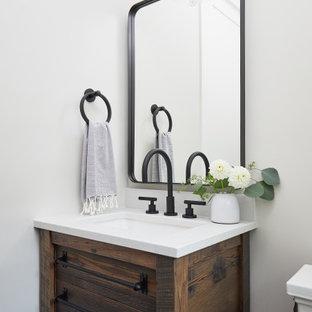 Kleine Landhaus Gästetoilette mit verzierten Schränken, dunklen Holzschränken, weißer Wandfarbe, braunem Holzboden, Quarzwerkstein-Waschtisch, weißer Waschtischplatte und freistehendem Waschtisch in Grand Rapids