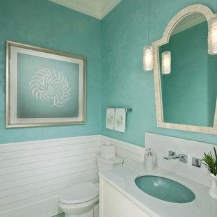 Maritime Gästetoilette mit flächenbündigen Schrankfronten, weißen Schränken, grüner Wandfarbe, Unterbauwaschbecken, grünem Boden und weißer Waschtischplatte in Miami