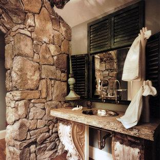 Foto di un bagno di servizio stile rurale di medie dimensioni con nessun'anta, ante con finitura invecchiata, WC monopezzo, pareti verdi, pavimento in legno massello medio, lavabo da incasso e top in pietra calcarea
