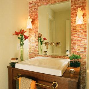 Idées déco pour un petit WC et toilettes contemporain avec une vasque, un placard en trompe-l'oeil, des portes de placard en bois sombre, un plan de toilette en bois, un mur orange, un carrelage orange et un plan de toilette marron.
