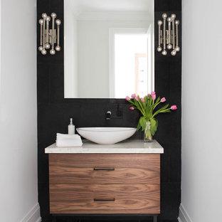 Ejemplo de aseo actual con armarios con paneles lisos, puertas de armario de madera oscura, lavabo sobreencimera, encimera de mármol, paredes negras y encimeras beige