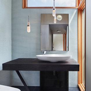 Идея дизайна: маленький туалет в современном стиле с биде, синей плиткой, стеклянной плиткой, синими стенами, полом из сланца, настольной раковиной, столешницей из дерева, черным полом, открытыми фасадами, темными деревянными фасадами и коричневой столешницей