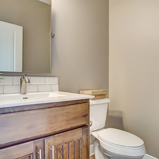 На фото: со средним бюджетом туалеты среднего размера в стиле кантри с фасадами с декоративным кантом, фасадами цвета дерева среднего тона, унитазом-моноблоком, белой плиткой, плиткой кабанчик, бежевыми стенами, паркетным полом среднего тона, монолитной раковиной, столешницей из искусственного кварца, коричневым полом и желтой столешницей