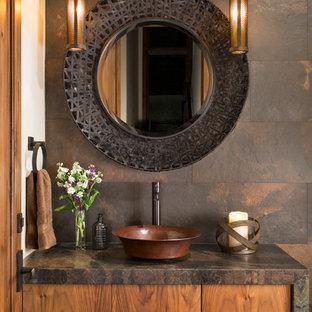 Rustikale Gästetoilette mit flächenbündigen Schrankfronten, hellbraunen Holzschränken, braunen Fliesen, Aufsatzwaschbecken, Schieferfliesen und brauner Waschtischplatte in Denver