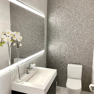 Modern inredning av ett mellanstort vit vitt toalett, med släta luckor, skåp i mörkt trä, en toalettstol med separat cisternkåpa, grå kakel, kakel i metall, grå väggar, marmorgolv, ett integrerad handfat, bänkskiva i kvarts och vitt golv