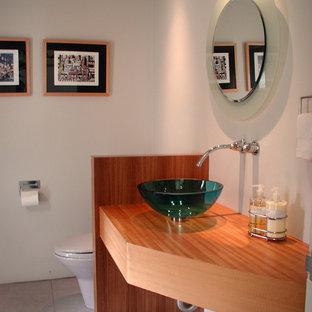 Idées déco pour un grand WC et toilettes moderne avec un placard sans porte, des portes de placard en bois brun, un WC séparé, un mur blanc, une vasque, un plan de toilette en bois et un plan de toilette marron.