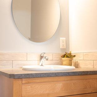 Cette photo montre un grand WC et toilettes chic avec un mur blanc, un sol en bois brun, un sol marron, un placard avec porte à panneau encastré, des portes de placard en bois brun, un WC séparé, un carrelage blanc, des carreaux de céramique, un lavabo posé, un plan de toilette en stratifié et un plan de toilette bleu.