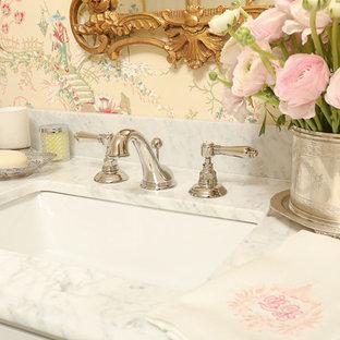 Idées déco pour un petit WC et toilettes classique avec un placard à porte vitrée, des portes de placard blanches, un WC séparé, un carrelage blanc, un mur rose, un sol en marbre, un lavabo encastré et un plan de toilette en marbre.