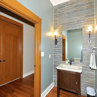 Classic cloakroom in Indianapolis with an integrated sink, freestanding cabinets, dark wood cabinets, a two-piece toilet, multi-coloured tiles, green walls, medium hardwood flooring and travertine tiles.
