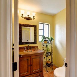 Идея дизайна: туалет в средиземноморском стиле с фасадами с утопленной филенкой, фасадами цвета дерева среднего тона, унитазом-моноблоком, желтой плиткой, желтыми стенами, полом из терракотовой плитки, врезной раковиной, столешницей из искусственного кварца, розовым полом и коричневой столешницей