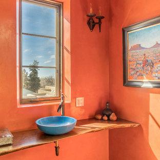 Cette photo montre un WC et toilettes sud-ouest américain avec un mur orange, un sol en bois brun, une vasque, un plan de toilette en bois, un sol beige et un plan de toilette marron.