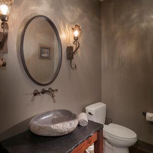 Cette image montre un petit WC et toilettes traditionnel avec une vasque, un placard sans porte, des portes de placard en bois brun, un plan de toilette en stéatite, un WC à poser, un mur marron et un sol en bois foncé.