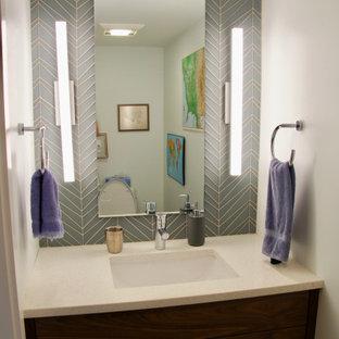 На фото: маленькие туалеты в современном стиле с плоскими фасадами, темными деревянными фасадами, унитазом-моноблоком, серой плиткой, стеклянной плиткой, белыми стенами, полом из керамической плитки, врезной раковиной, столешницей из искусственного кварца, серым полом и белой столешницей