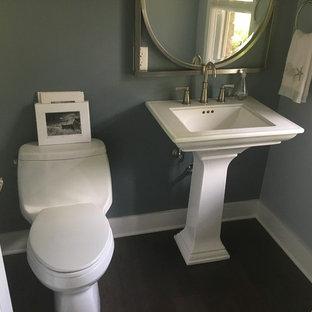 Immagine di un piccolo bagno di servizio stile marino con WC monopezzo, pareti blu, parquet scuro, lavabo a colonna e pavimento marrone