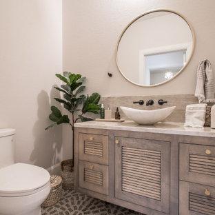 他の地域のトランジショナルスタイルのおしゃれなトイレ・洗面所 (テラゾーの床、ベージュの床、ルーバー扉のキャビネット、茶色いキャビネット、分離型トイレ、白い壁、ベッセル式洗面器、造り付け洗面台) の写真