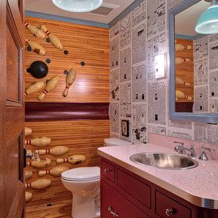 Diseño de aseo ecléctico con armarios con paneles lisos, puertas de armario rojas, sanitario de dos piezas, suelo de madera en tonos medios, lavabo encastrado, suelo marrón y encimeras rojas