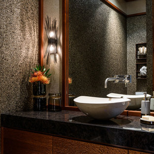 Photo of a medium sized world-inspired cloakroom in Hawaii with multi-coloured walls, limestone flooring, a vessel sink and engineered stone worktops.