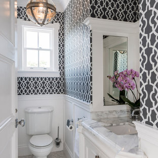 Photo of a traditional powder room in Brisbane with recessed-panel cabinets, white cabinets, a two-piece toilet, mosaic tile floors, an undermount sink and grey floor.