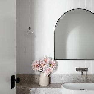 メルボルンのコンテンポラリースタイルのおしゃれなトイレ・洗面所 (フラットパネル扉のキャビネット、黒いキャビネット、壁掛け式トイレ、白いタイル、ミラータイル、白い壁、オーバーカウンターシンク、ライムストーンの洗面台、グレーの洗面カウンター) の写真