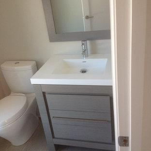 Свежая идея для дизайна: маленький туалет в стиле модернизм с плоскими фасадами, серыми фасадами, белыми стенами, монолитной раковиной, столешницей из искусственного камня и раздельным унитазом - отличное фото интерьера
