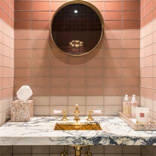 他の地域の小さいトラディショナルスタイルのおしゃれなトイレ・洗面所 (ピンクのタイル、ピンクの壁、大理石の洗面台、マルチカラーの洗面カウンター) の写真