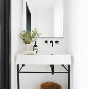 Modelo de aseo contemporáneo, pequeño, con armarios abiertos, suelo de azulejos de cemento, suelo azul, paredes blancas y lavabo tipo consola