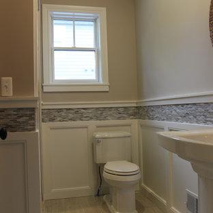 Ispirazione per un bagno di servizio stile americano di medie dimensioni con WC a due pezzi, piastrelle grigie, piastrelle di vetro, lavabo a colonna, pavimento beige, pareti beige e pavimento in gres porcellanato