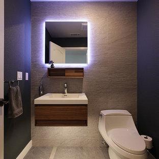 Стильный дизайн: маленький туалет в современном стиле с плоскими фасадами, темными деревянными фасадами, унитазом-моноблоком, серой плиткой, керамогранитной плиткой, зелеными стенами, полом из керамогранита, монолитной раковиной, столешницей из искусственного камня, серым полом и белой столешницей - последний тренд