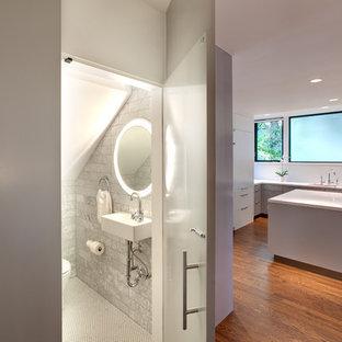 Ejemplo de aseo actual con lavabo suspendido, baldosas y/o azulejos grises y baldosas y/o azulejos de piedra