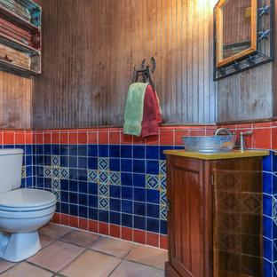 Aménagement d'un grand WC et toilettes sud-ouest américain avec un WC séparé, un carrelage marron, un carrelage bleu, un carrelage orange, un carrelage multicolore, des carreaux de porcelaine, un sol en carrelage de porcelaine, un lavabo encastré, un plan de toilette en granite, des portes de placard en bois brun, un mur multicolore, un placard en trompe-l'oeil et un plan de toilette jaune.