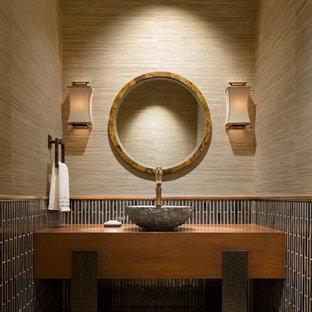Modelo de aseo contemporáneo con armarios abiertos, puertas de armario de madera oscura, baldosas y/o azulejos marrones, azulejos en listel, paredes marrones, lavabo sobreencimera y suelo beige