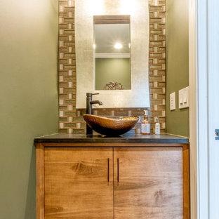Свежая идея для дизайна: маленький туалет в стиле ретро с плоскими фасадами, фасадами цвета дерева среднего тона, унитазом-моноблоком, разноцветной плиткой, стеклянной плиткой, зелеными стенами, полом из керамической плитки, настольной раковиной, столешницей из искусственного кварца, бежевым полом и черной столешницей - отличное фото интерьера