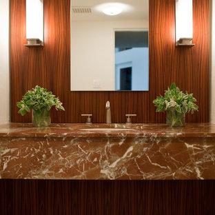 Idee per un ampio bagno di servizio minimalista con nessun'anta, WC monopezzo, pavimento in pietra calcarea, lavabo sottopiano e top in onice